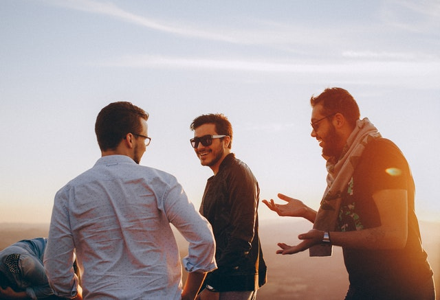 tři muž jdou, mají brýle, v pozadí svítí slunce, někdo je tam ještě skrčený, smějí se a vykládají