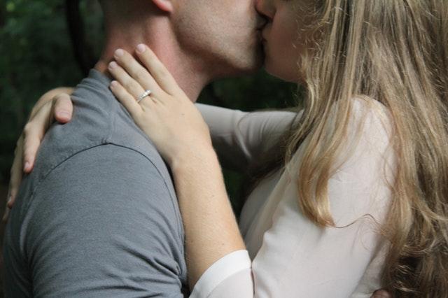 muž a žena polibek, ona má ruku na jeho krku, má prstýnek a světlou halenku