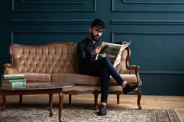muž s novinami sedící na pohovce
