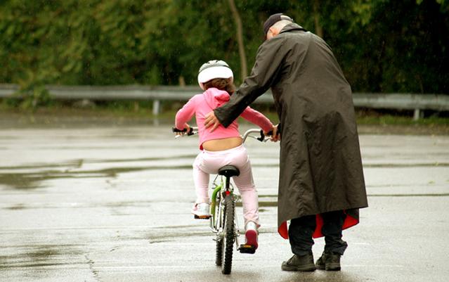 starší muž v plášti učí malou holčičku jezdit na kole