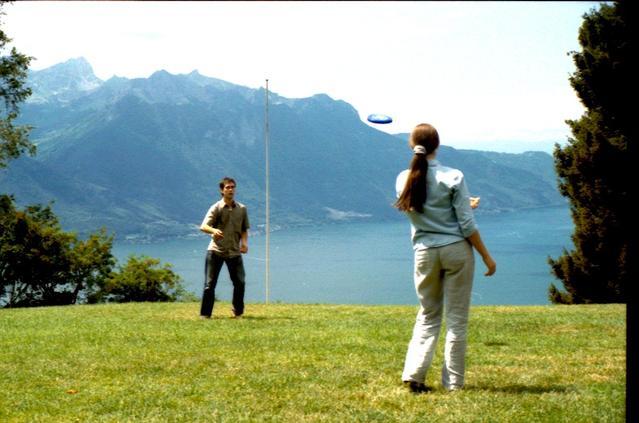 dva lidé na louce v pozadí jsou hory a voda, si házejí freezbee