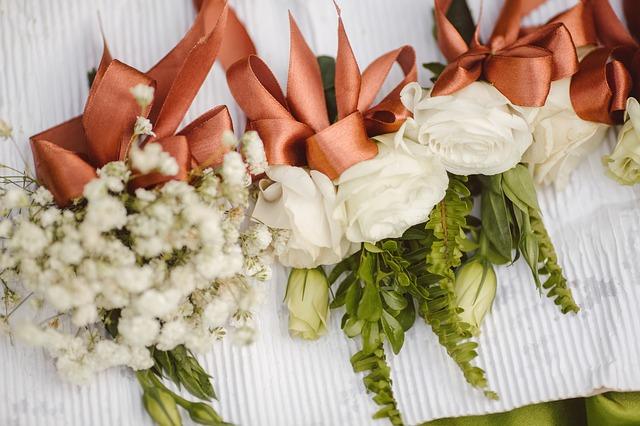 bílé růže a další bílé květiny, svázané bronzovou mašlí společně s dalšími zelenými lístky do jednotlivých kytiček