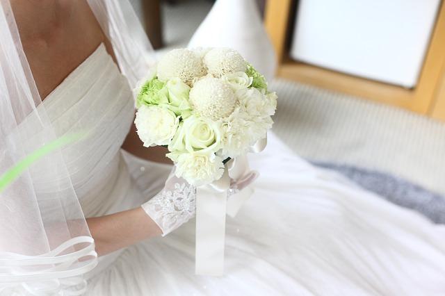 nevěsta sedí a drží v ruce bílou kytici, má rukavičky závoj